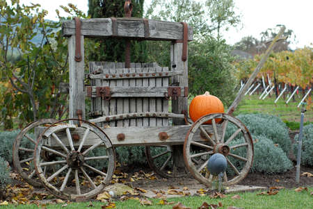 A bright orange pumpkin sitting on top of an old, rustic wooden cart. photo