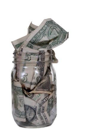 dollar bills: A glass jar stuffed with dollar bills.  Isolated on white. Stock Photo