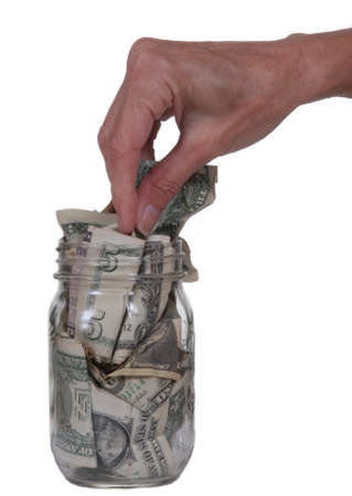 retirement fund: Female hand taking dollar bills out of glass jar.  Isolated on white.