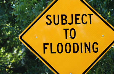 Yellow warning sign which reads: Subject to Flooding photo