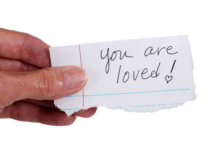 Close up of a hand holding a note with the words: 'You Are Loved'.  Isolated on white.  photo