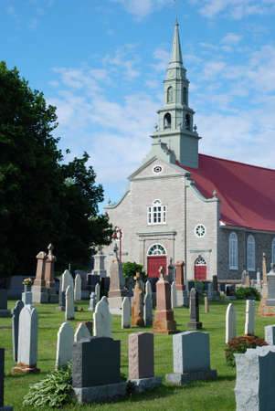 An old church with cemetery gravestones.  Blue sky, clouds.