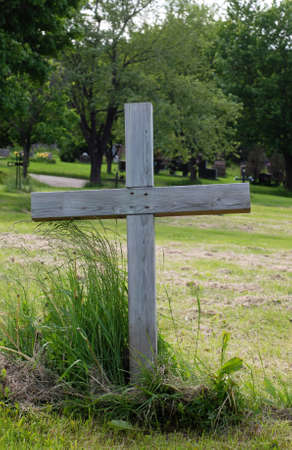 Simple, single wooden cross at a gravesite in an outdoor cemetery. Stock Photo