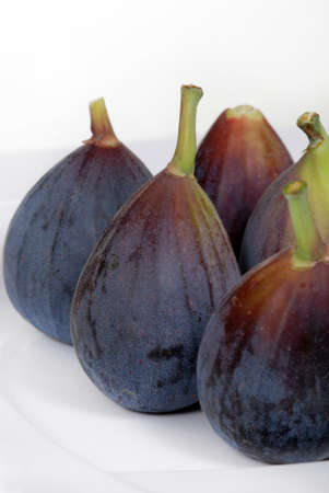 Fresh, organic, whole, purple figs on a white plate.  Shallow depth of field.