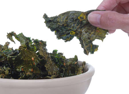 kale: Kale chips in a bowl with a hand holding one.  Isolated on white.