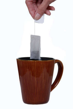 Female hand holding a tea bag above a brown ceramic cup.  Isolated on white.
