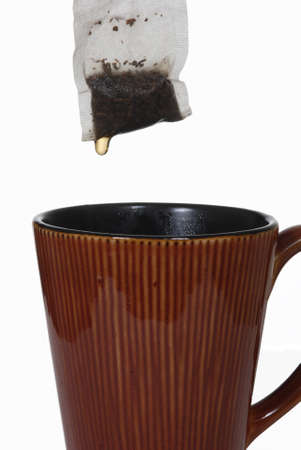 A wet tea bag with a drip held above a ceramic mug.  Isolated on white.