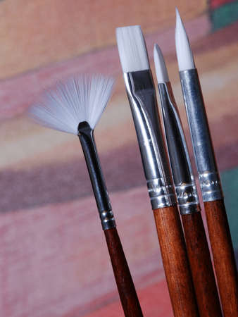 A clean, new, white set of artists paint brushes with painted canvas in background. Stock Photo