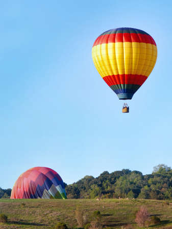 Hot air balloons landing in green hills with trees