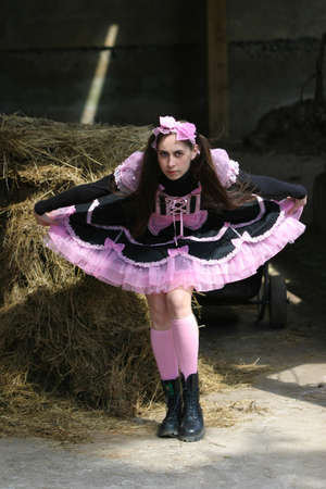 cosplay: A girl in gothic lolita outfit posing ahead of heystack
