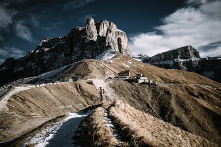 A trail in the mountains leading towards a hut. A person is standing at the end of the trail. The Scene is shot at the Gardena Pass in the Dolomites, Northern Italy. Stock Photo