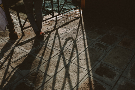 photgraphy: A person is leanin on a balustrade. The sunset creates a long shadow on the ground. The scene is shot in Venice, Italy. Stock Photo