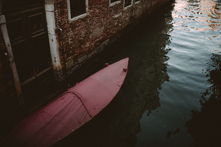 photgraphy: A boat with a red cover in a canal in Venice, Italy.
