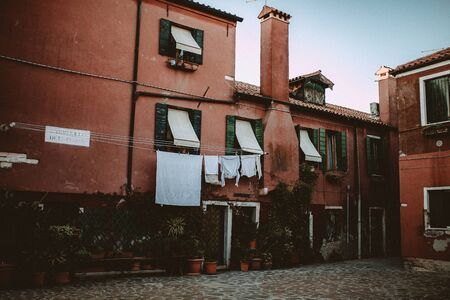 photgraphy: A Square with red houses in Venice, Italy. Linen are hanging from the Windows. Stock Photo