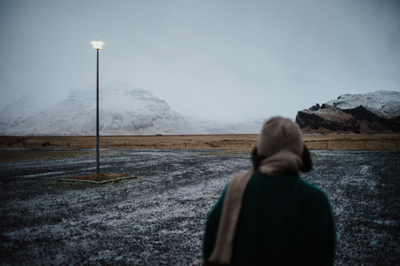 A person walking in front of some mountains in Iceland