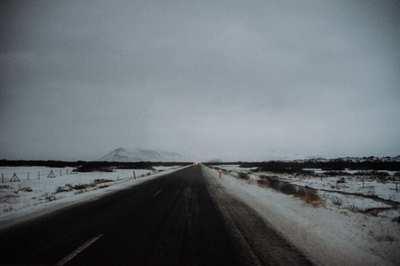 A straight road leading through a snow covered field in Iceland