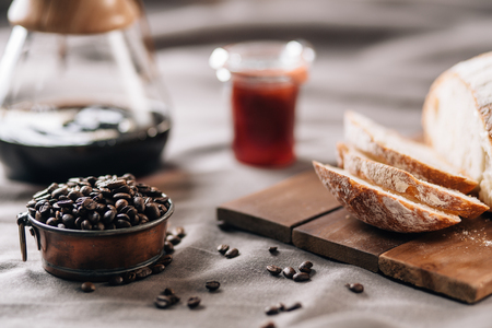 A tabletop scene with coffee beans in a pot, some bread, jam and coffee on a table cloth