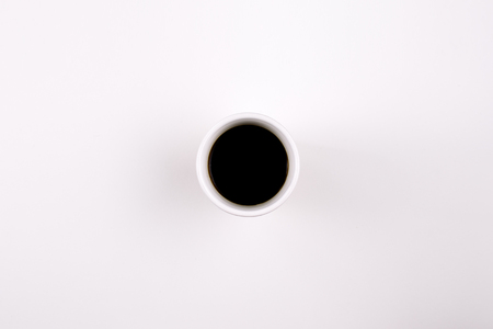 A coffee mug with black coffee in it on light background