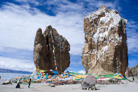 megalith: Megalith by the Namtso Lake in Tibet, China. Prayer Flags with five colors front the megalith, and white khatas which consecrate to the god of lake on the megalith.