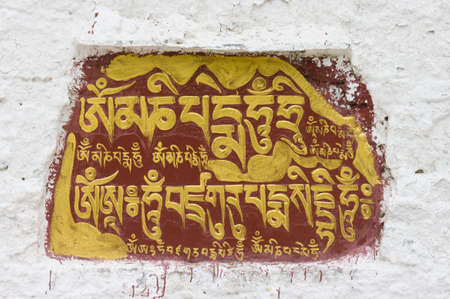 sanskrit: The Sanskrit mantra Om mani padme hum inscribed and painted on a mani stone embedded in a wall of the Potala Palace in Lhasa, Tibet, China.