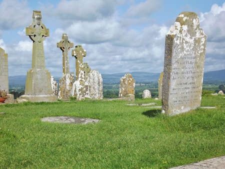 head stones: Rural cemetery in Ireland with fields and mountains behind Editorial