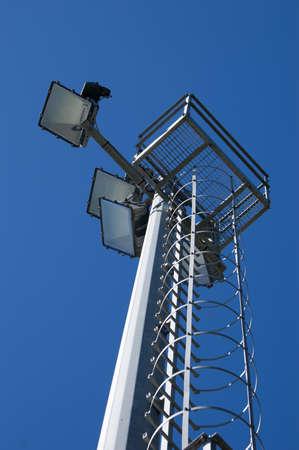 Lights on a pylon under a blue sky photo