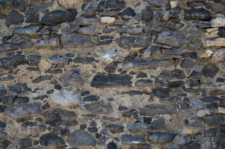 A wall of aged grey stones in line  photo