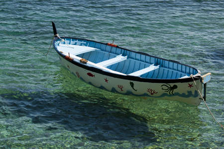 An old colored rowboat anchored in the sea photo