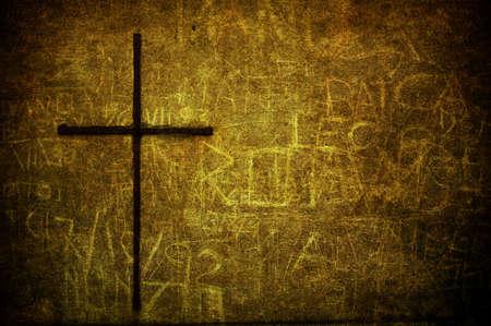 金属製のクロスとひびの入った黄色のグランジ壁