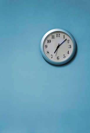A blue and white clock on a blue wall photo