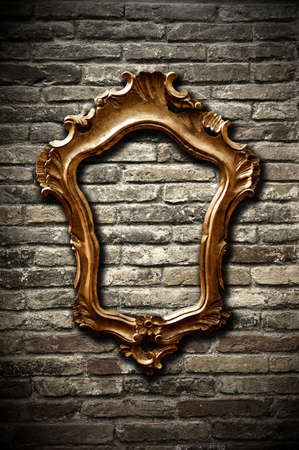A vintage golden frame on a dark brick wall