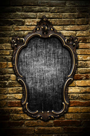 A vintage golden frame on a dark brick wall Stock Photo - 8017673