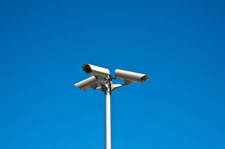 Three security cameras isolated on a blue sky photo