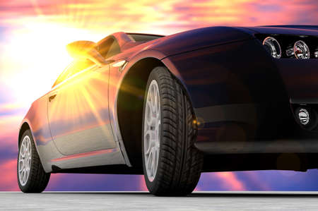 A black car seen in front with a sunset back