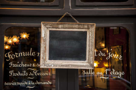 A blackboard in a frame on a restaurant window photo