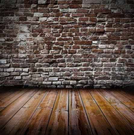 Grunge vecchio interno con il muro di mattoni e pavimento in legno