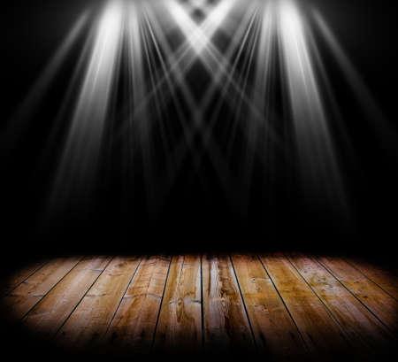 Due spot light su un pavimento di legno e uno sfondo nero