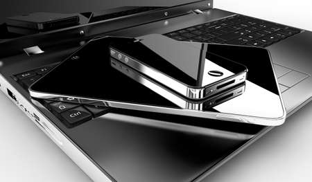 A tablet and a phone on a laptop