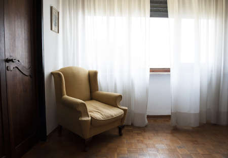 A brown armchair in an old apartment with wooden floor photo