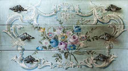 Detail of drawer carving with flowers and handles photo