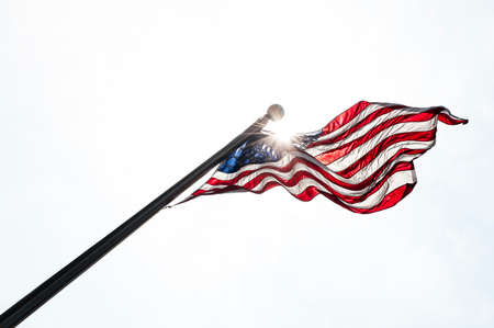 waving flag: Usa flag in the sky with sun rays Stock Photo