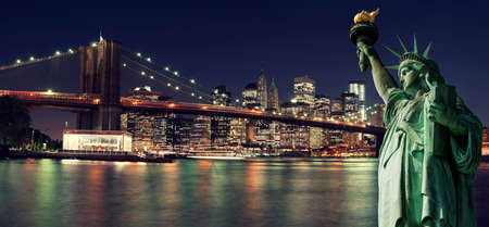 cityscapes: Brooklyn Bridge and The Statue of Liberty at Night, New York City Stock Photo