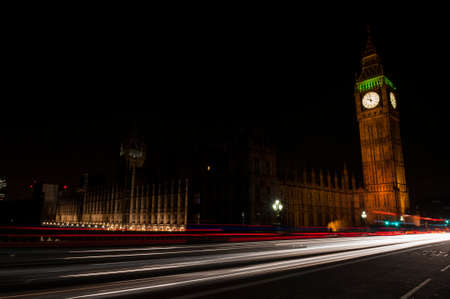 Big Ben, one of the most prominent symbols of both London and England, as shown at night along with the lights of the cars passing by photo