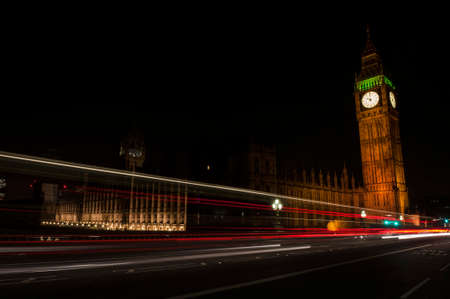 Big Ben one of the most prominent symbols of Both London and England as shown at night along with the lights of the cars passing by photo