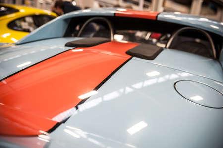 internships: Back of a blue sport car illuminated in a salon Stock Photo