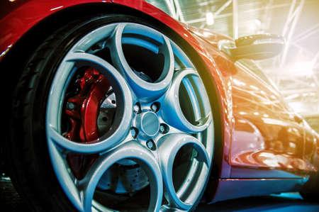 Red modern sport car illuminated in a salon