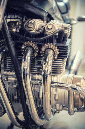 exhaust pipe: Aged motorcycle engine detail with chrome exhaust pipe Stock Photo