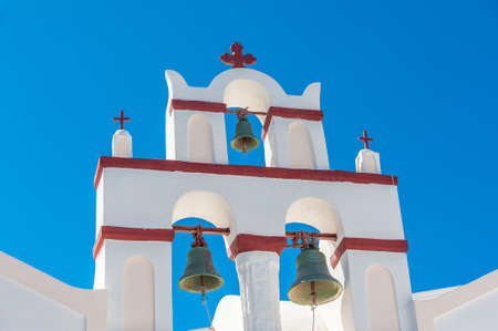White and red bells tower over a blue sky in Santorini - Greece