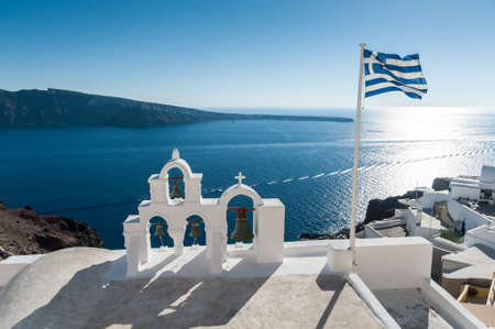 Top of orthodox church with greece flag in Santorini - Greece