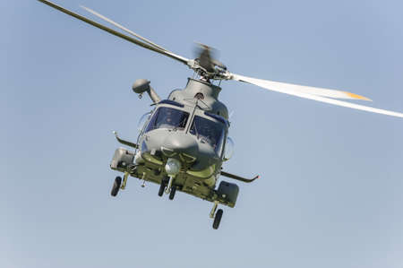 Military helicopter fliyng in the blue sky Archivio Fotografico
